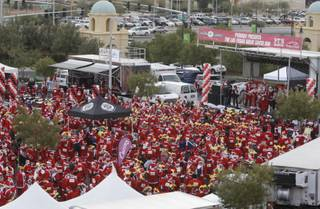 Runners dressed as Santa Claus listen to music and entertainment before the Las Vegas Great Santa Run Saturday, Dec. 5, 2009,  in Las Vegas, Nev. The annual 5K charity run, a warmup to the Las Vegas Marathon, tries to break the Guinness World Record for a Santa gathering. The current record is 12,965 Santas.