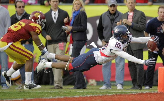 Arizona wide receiver Juron Criner, right, dives into the end zone to score a touchdown against Southern California during the second half of their NCAA college football game in Los Angeles, Saturday, Dec. 5, 2009. At left is USC's Josh Pinkard. Arizona won 21-17.