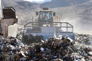 An operator drivers a compacter over garbage at the Apex landfill northeast of Las Vegas Monday, November 23, 2009.