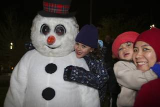 Kailee Fisher, 6, gives Frosty the Snowman a big hug Friday night during the WinterFest celebration at the Henderson Events Plaza.  Standing to the right is Virgie Rosal and her son, Isaac, 2.