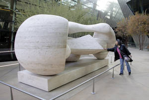 "Lily Chen, a tourist from Taiwan, touches ""Reclining Connected Forms,"" a Henry Moore sculpture at CityCenter Tuesday, December 15, 2009."