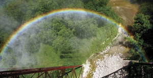 As a train engine releases steam, a rainbow is formed high above the Des Moines River near Boone, Iowa.
