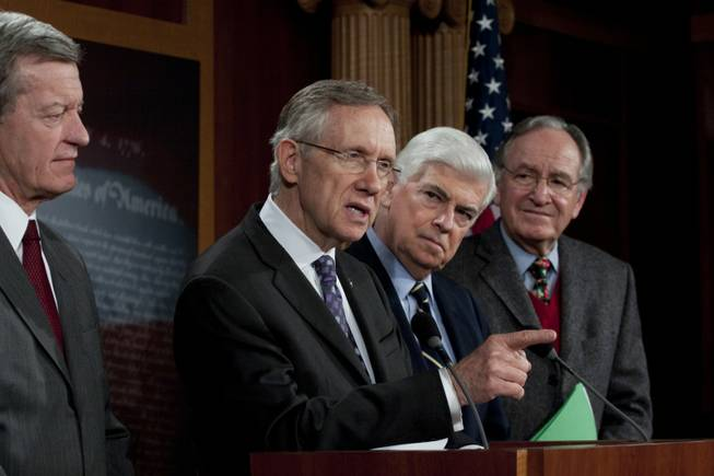 Senate Majority Leader Harry Reid, D-Nev., speaks to reporters as Sen. Max Baucus, D-Mont., left, Sen. Christopher Dodd, D-Conn., and Sen. Tom Harkin, D-Iowa, listen, on Capitol Hill Saturday (Dec. 19, 2009)  in Washington, D.C.