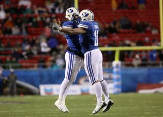 Max Hall (left) and Manase Tonga celebrate after a BYU touchdown during the MAACO Bowl Las Vegas Tuesday at Sam Boyd Stadium.  BYU dominated Oregon St. with a 44-20 win.