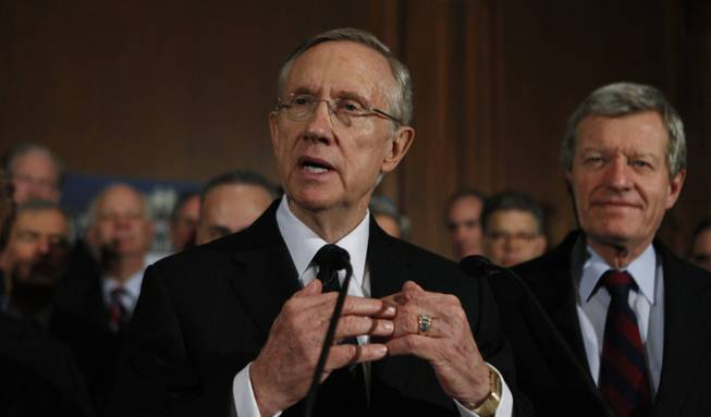 Senate Majority Leader Harry Reid of Nev., left, accompanied by Senate Finance Committee Chairman Sen. Max Baucus, D-Mont., right, and Senate Democrats, gestures during a health care news conference on Capitol Hill in Washington, Wednesday, Dec. 23, 2009.