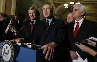 Senate Majority Leader Harry Reid of Nevada, center, answers questions outside of the Senate chambers on Capitol Hill in Washington, Thursday, Dec. 24, 2009, after the Senate passed the health care reform bill. From left are, Senate Finance Finance Committee Chairman Sen. Max Baucus, D-Mont., Reid, Senate Majority Whip Richard Durbin of Ill., and Senate Banking Committee Chairman Sen. Christopher Dodd, D-Conn.