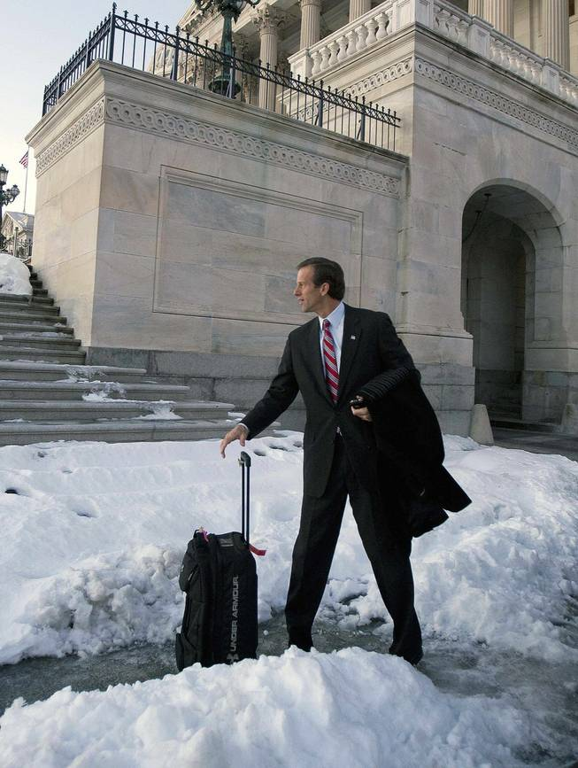Sen. John Thune, R-S.D, waits for his ride in the snow outside of the Capitol in Washington, Thursday, Dec. 24, 2009, after the Senate passed the health care reform bill.