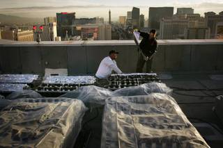 Pyrotechnicians Jim Stannard, left, and Carlton Siple from Fireworks by Grucci, a company based in Long Island, New York, put aluminum foil over the fireworks that are part of the finale for New Year's Eve on the roof of Treasure Island in Las Vegas Wednesday, December 30, 2009.