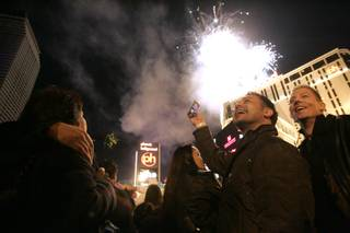 Jimmie Gleeson, center, and Blair Hanloh smile and take photos as fireworks explode off Planet Hollywood as they ring in the new year on the Strip.