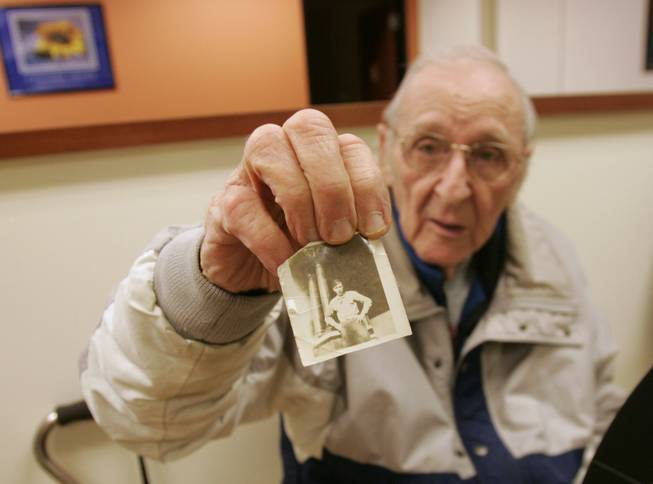 Vincent Cravero, a client at the center for adults, shows a photo of himself when he was in the Army during World War II.
