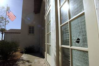 A bullet hole is seen in the window of the 5th Street School Tuesday, January 5, 2010 as a result of the previous day's shoot out that killed a court security officer and the gunman and injured a deputy U.S. marshall.