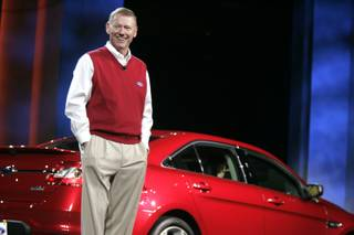 Ford CEO Alan Mulally speaks during the keynote address with a 2010 Ford Taurus behind him during the Consumer Electronics Show at the Hilton Center in Las Vegas Thursday, January 7, 2010.