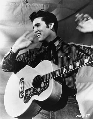 Elvis Presley poses with his Gibson J-200 guitar in an MGM studio publicity photo from the 1950s. Presley will be reunited with Sun Records as part of a licensing agreement between the owner of the historic label and the singer's estate. Sun Entertainment Corp. of Nashville announced the agreement with Elvis Presley Enterprises Inc. Thursday, Oct. 12, 2006.
