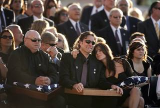 Steven Bentley Cooper, left, and Marshall Cooper, who is being comforted by his wife, sit in the front row during the funeral services for their father, the slain court security officer Stanley Cooper outside of Central Christian Church in Henderson Monday, January 11, 2010.