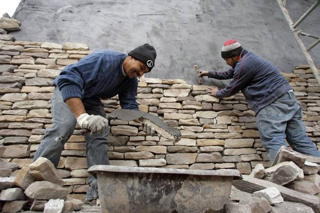 Oscar Rugamas, left, and Elmer Lara of Alvarez Masonry place stones on the exterior of a New American Home on Jan. 8 at 2911 Bella Kathryn Circle. Lack of financing for the project, which was supposed to be completed for next week's International Builders' Show, helped drive builder Domanico Custom Homes out of business.