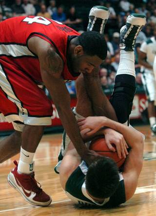 UNLV's Darris Santee, left, tries to wrestle the ball away from Colorado State's Travis Busch during basketball action in Fort Collins, Colo., on Wednesday. UNLV won the game 80-72.