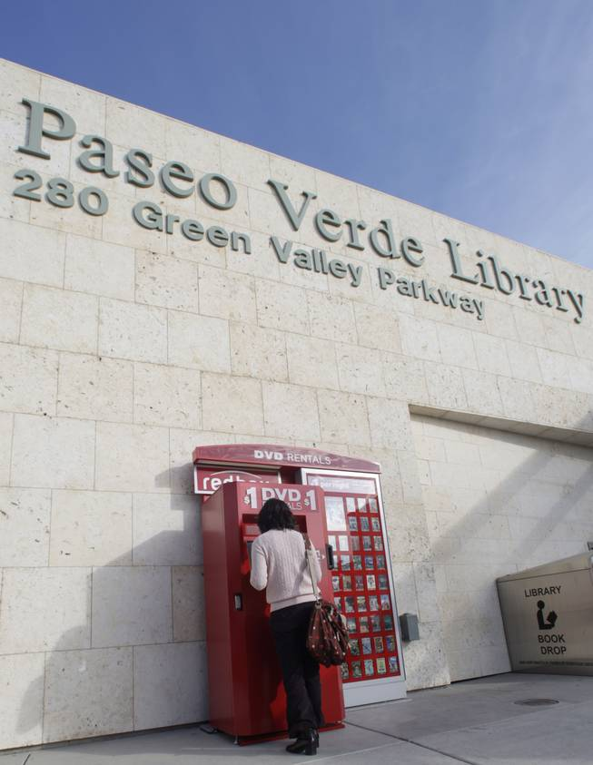 Amy Choi checks the selection of movies at a Redbox DVD movie kiosk in front of the Paseo Verde Library in Henderson on Tuesday. The Paseo Verde Library and the Green Library recently added the rental kiosks.