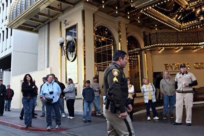 A crowd gathers at the Four Queens valet entrance near the scene of a fatal crash at the Fremont Street Experience in downtown Las Vegas on Tuesday, Jan. 26, 2010.