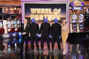 Pat Sajak and Vanna White flank the Blue Man Group on the set of <em>Wheel of Fortune</em>.