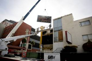 YESCO workers remove the Queen of Hearts Hotel sign after the demolition ceremony for the hotel, part of the ongoing construction to build a new City Hall and office complex in downtown Las Vegas Tuesday, February 2, 2010. The sign will be stored at the Neon Boneyard.
