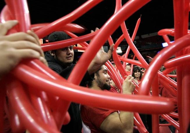 Red ballons are passed out to the student section before the start of UNLV's game against New Mexico on Wednesday, Feb. 10, 2010, at the Thomas & Mack Center.