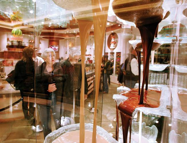 Shoppers examine the chocolate fountain at Jean-Philippe Patisserie at the Bellagio.