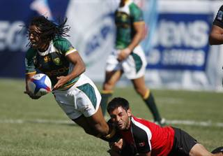 South Africa's Cecil Afrika passes as he is taken down by Canada's Philip Mack during the USA Sevens World Series rugby tournament, Saturday, Feb. 13, 2010, in Las Vegas.
