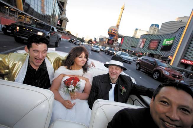 Elvis impersonator Roddy Ragsdale entertains Lynn Hassell, 46, and Neil Cawkwell, 45, of Ascot, England, during their ride along the Las Vegas Strip last month after being married at the Little White Wedding Chapel. Driver Oscar Villegas is at right.