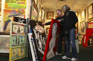 Bill and Sarah Turner, of Ohio, peruse the paintings of the late artist Steve Kaufman on display Sunday, Feb. 14, at the Centaur Art Gallery in the Fashion Show Mall. Kaufman, 49, of Sherman Oaks, Calif., was found dead Feb. 12 in Vail, Colo.