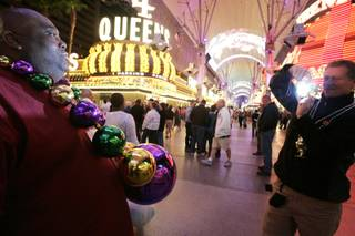 Jeff Keen, left, of St. Louis poses for a photo taken by Scott Sheen, right, who is trying to sell him the large Mardi Gras beads Keen is wearing, during Fat Tuesday celebrations at the Fremont Street Experience in downtown Las Vegas Tuesday, February 16, 2010.