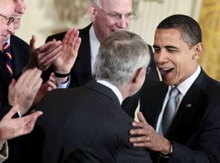 U.S. President Barack Obama, right, is congratulated by Senate Majority Leader Harry Reid, center, after signing the Omnibus Public Lands Management Act of 2009, in the East Room of the White House in Washington, D.C., on March 30, 2009.