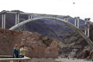 Jason and Rachel Burger of Lynchburg, Virginia take photo at an overlook of the Hovver Dam, with the bypass bridge construciton in the background, outside Boulder City Friday, February 26, 2010.