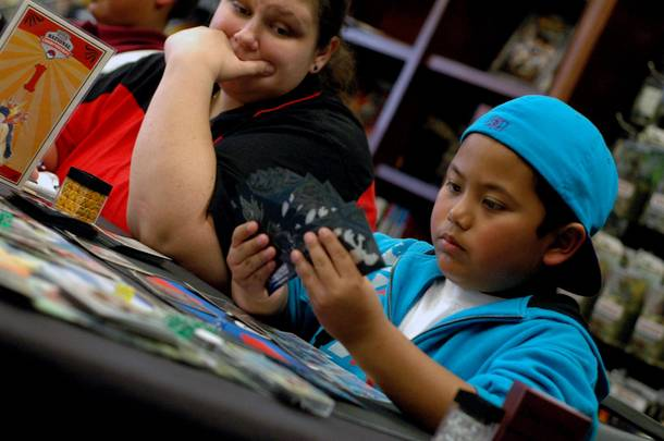 A judge watches 8-year-old Patrick Martinez during the junior division championship round of the Pokemon Trading Card Game Nevada State Championship.