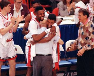 UNLV players Moses Scurry, left, and Anderson Hunt hug coach Jerry Tarkanian after their 103-73 victory over Duke in the NCAA Final Four Championship game, April 2, 1990, in Denver.
