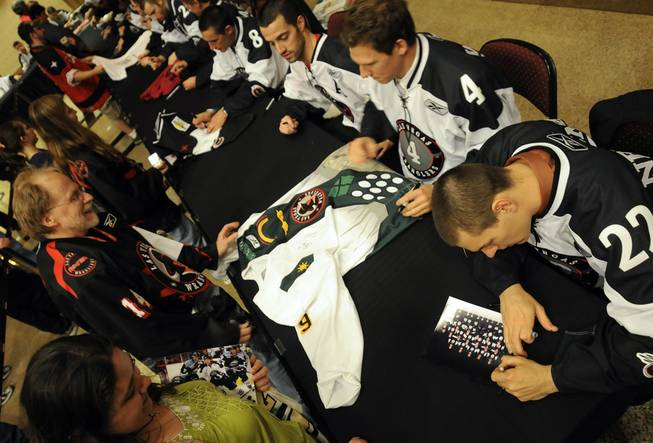 Wranglers players autograph memorabilia during Fan Appreciation Night at the Orleans Arena on Saturday, April 3, 2010.