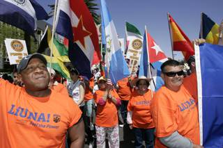 Members and supporters of Laborers' International Union North America carry flags of different nations at a rally for immigration reform Saturday, April 10, 2010 outside the Lloyd George Federal Building.