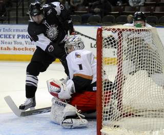 Ryan Weston slips the puck through the five hole of Utah goalie Mike Morrison for a first period goal on Sunday afternoon at the E-Center in West Valley City.