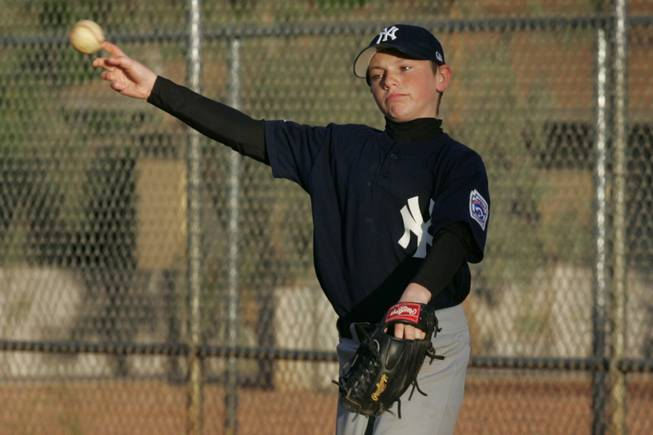 Justin Rasavage warms up during a Peccole Little League game Wednesday, April 21, 2010.