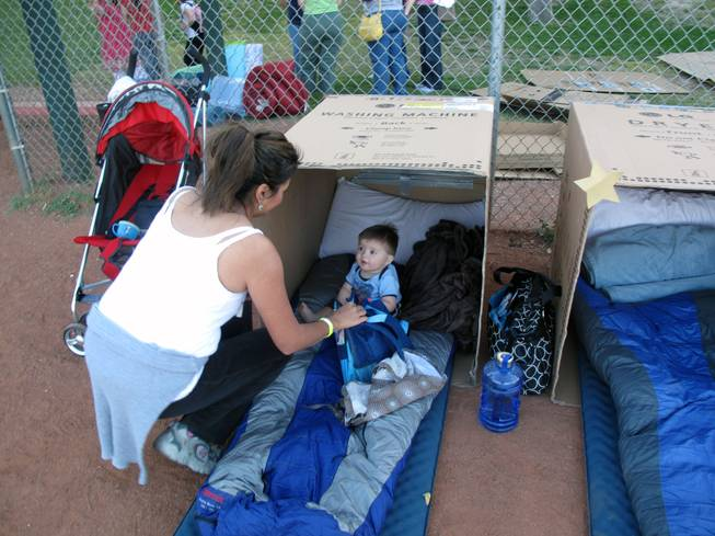 Rene Barton puts her 9-month-old son, Matthew, in the cardboard box the two will call home for one night to learn what it feels like to he homeless.