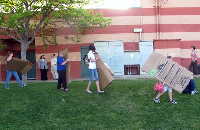 A group of volunteers carry their cardboard boxes to get ready to sleep outside as part of a fundraiser for Family Promise at the Boys and Girls Club.