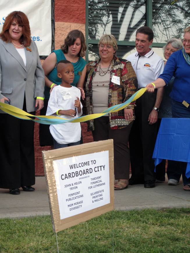 James Kelly, age 7, prepares to cut the ribbon to open Cardboard City, where he will be mayor for the night, at a fundraiser for Family Promise.