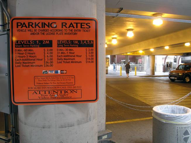 A sign near the passenger pickup area shows the fees to park at McCarran International Airport's parking lots with the new Express Exit pay system.