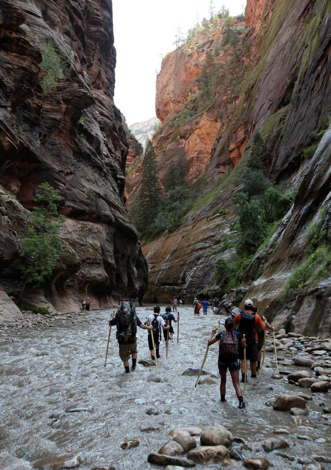 In this Sept. 5, 2009 file photo, hikers wade through the Virgin River at the entrance to The Narrows in Zion National Park, Utah. Officials say two Las Vegas men were found dead this week in the area.