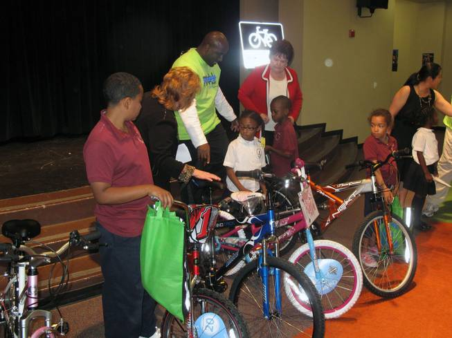 Look Out Kids About President Robin Munier, Councilman Ricki Barlow and Councilwoman Lois Tarkanian show kids the bicycles the youngsters won at a Nevada Moves Day event at Agassi Prep.