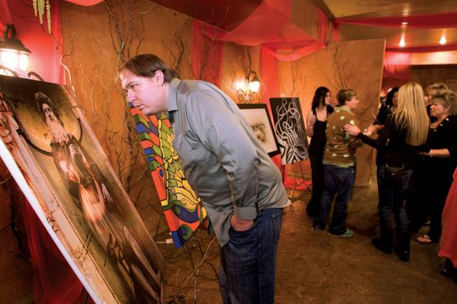 "Nathan Harvey looks over ""Port of DaVinci"" by artist Max Lightbender during the ARTrageous Vegas 7th Annual Art Show at the Aruba."