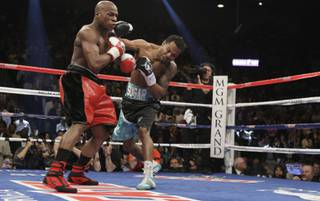 Floyd Mayweather Jr. (L) takes a punch from Shane Mosley during their welterweight fight Saturday at the MGM Grand Garden Arena.
