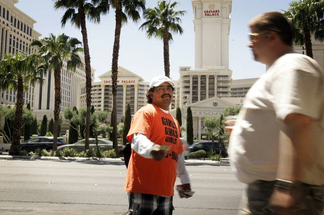 A handbiller outside the Flamingo just north of Flamingo Road on the Strip passes out cards for an escort service in May 2010.