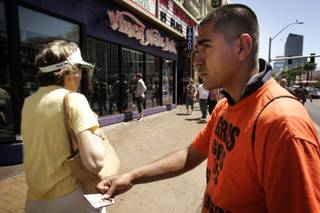 A handbiller passes out cards in May 2010 for an escort service on The Strip just north of Flamingo Road, outside the Flamingo.