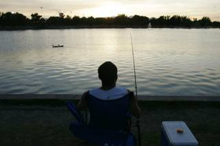 David Rivero watches the evening sky while fishing Thursday at Sunset Park .