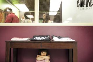 Four-year-old Isabella Villamil hides under a table outside Empire Gallery during the soft opening of Emergency Arts on Friday, May 7, in downtown Las Vegas.